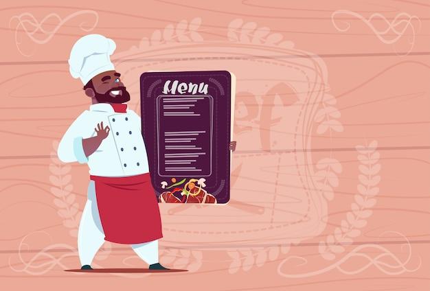 African american chef cooka gospodarstwa menu restauracji smiling cartoon chief in white uniform over wooden textured background