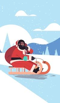 African american santa z maską jeżdżącą na sankach szczęśliwego nowego roku wesołych świąt bożego narodzenia koncepcja uroczystości zimowy krajobraz tło wektor ilustracja pionowa