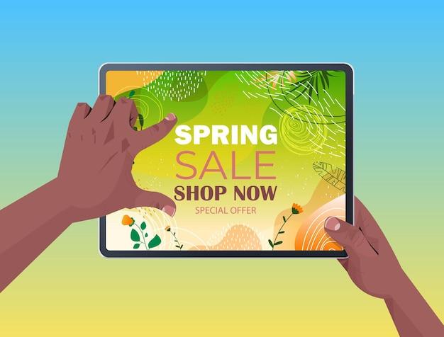 Afroamerykanie ludzkie ręce za pomocą tabletu z ulotką baner sprzedaży wiosny lub kartkę z życzeniami na poziomej ilustracji ekranu