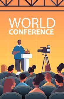 Afroamerykanin biznesmen wygłasza przemówienie na trybunie z mikrofonem na korporacyjnej międzynarodowej konferencji światowej sali wykładowej wnętrza pionowej ilustracji