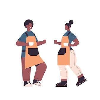 Afroamerykanin kobieta mężczyzna w mundurze pracuje w kawiarni kelnerów w fartuchu obsługujących kawę pełnej długości na białym tle ilustracji wektorowych