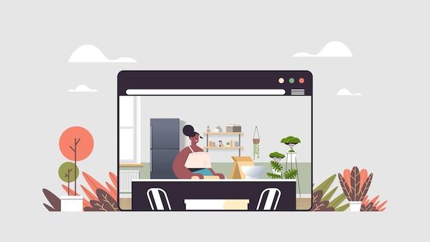 Afroamerykanin kobieta przygotowywanie potraw w domu koncepcja gotowania online nowoczesna kuchnia wnętrze okno przeglądarki internetowej portret poziomy