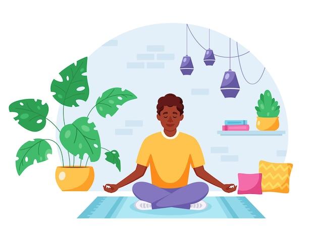 Afroamerykanin medytujący w pozie lotosu we wnętrzu loftu