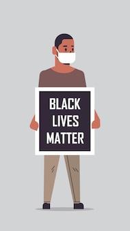 Afroamerykanin w masce trzymający czarną materię życia kampania transparentu przeciwko dyskryminacji rasowej, wspieranie równych praw