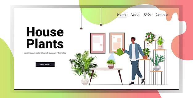 Afroamerykanin z konewką opiekuje się roślinami domowymi w salonie lub w przydomowym ogrodzie