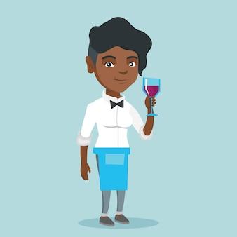 Afroamerykańska kelnerka trzyma kieliszek wina.