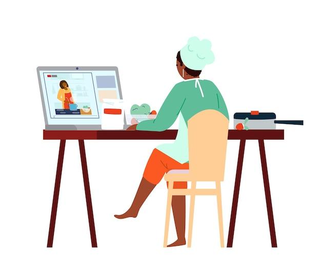 Afroamerykańska kobieta w kapeluszu szefa kuchni i fartuchu, oglądając lekcje gotowania online na laptopie.
