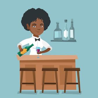Afrykańska barman stoi przy kontuarem barowym.