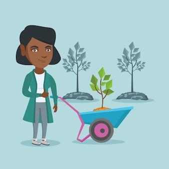 Afrykańska kobieta pcha taczki z rośliną.