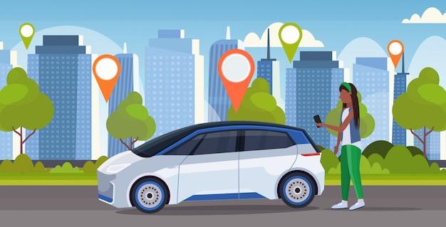 Afrykańska kobieta używa mobilną aplikację zamawia samochodu pojazd z lokaci oceny czynszu udostępniania samochodu pojęcia transportu carsharing usługa nowożytnym pejzażu miejskiego tłem horyzontalnym