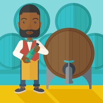 Afrykański producent wina sprawdza wino z beczki.