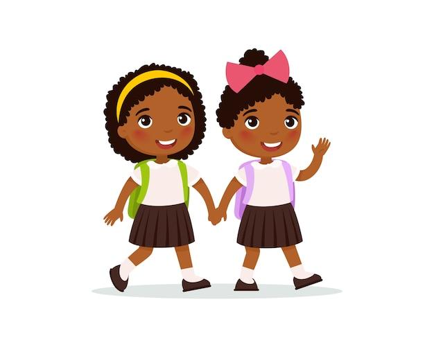 Afrykańskie uczennice chodzą do szkoły płaska ilustracja. para uczniów w mundurze, trzymając się za ręce na białym tle postaci z kreskówek. dwóch szczęśliwych uczniów szkoły podstawowej z plecakami macha ręką