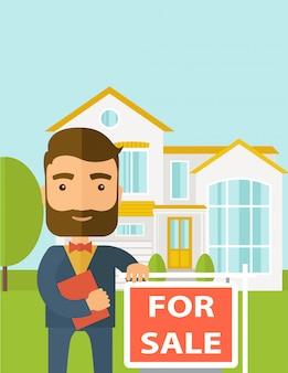 Agent nieruchomości stojący przy tabliczce na sprzedaż.
