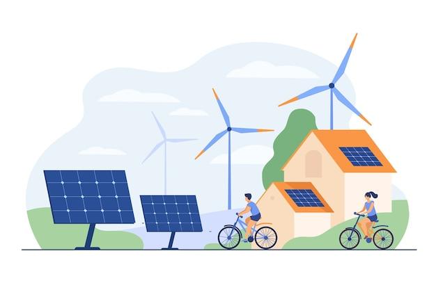 Aktywni ludzie na rowerach, wiatrakach i domu z panelem słonecznym na płaskiej ilustracji na dachu.