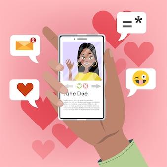 Aplikacja randkowa online. ręka trzyma telefon komórkowy z osobą płci żeńskiej na ekranie. wysłanie serca do dziewczyny i prośba o randkę. poszukiwanie romantycznego związku. ilustracja