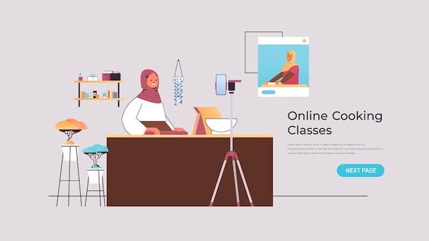 Arabka blogerka kulinarna przygotowująca danie podczas oglądania samouczka wideo z arabskim szefem kuchni w oknie przeglądarki internetowej