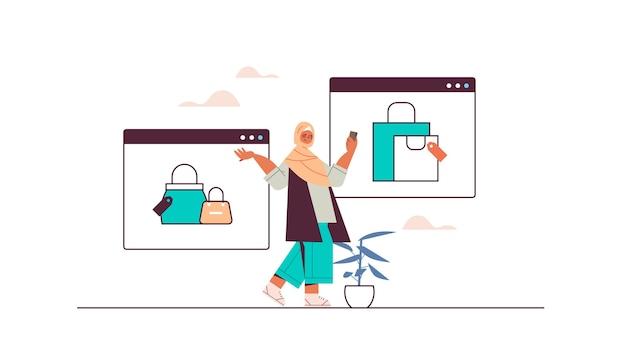 Arabka za pomocą smartfona kupuje i wybiera rzeczy w sklepie internetowym sprzedaż konsumpcjonizm zakupy online e-commerce inteligentne zakupy
