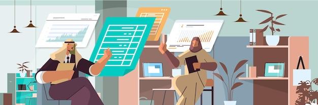 Arabscy biznesmeni analizujący dane statystyczne na wirtualnych tablicach pomyślna koncepcja pracy zespołowej wnętrze biurowe portret poziomy ilustracja wektorowa