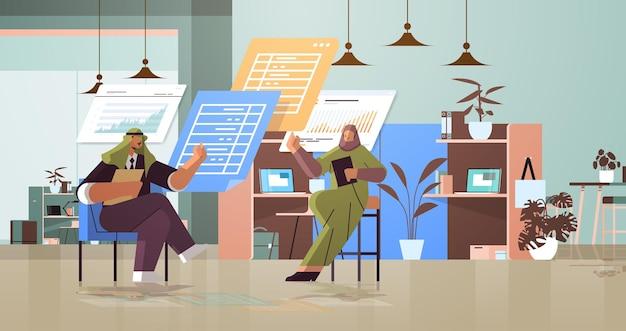 Arabscy biznesmeni analizujący dane statystyczne na wirtualnych tablicach pomyślna koncepcja pracy zespołowej