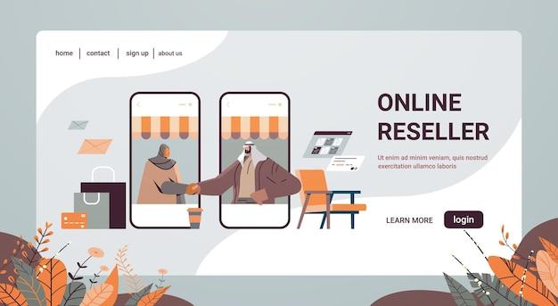 Arabscy biznesmeni ściskający dłonie partnerom biznesowym na ekranie smartfonów