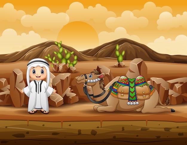 Arabscy chłopiec z wielbłądem odpoczywa na pustyni
