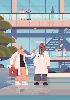 Arabscy lekarze w mundurach arabskich pracowników medycznych omawiających podczas spotkania koncepcja medycyny opieki zdrowotnej budynek szpitala na zewnątrz pionowy