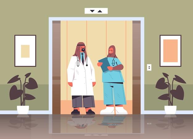 Arabscy pracownicy medyczni omawiający podczas spotkania w windy szpitalnej koncepcja medycyny medycyny arabscy lekarze w mundurze poziomym