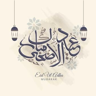 Arabska kaligrafia eid ul adha mubarak z wiszącymi lampionami na beżowym tle.