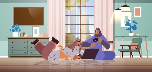 Arabska para z kartą kredytową za pomocą laptopa koncepcja zakupów online mężczyzna kobieta zamawiający towary razem