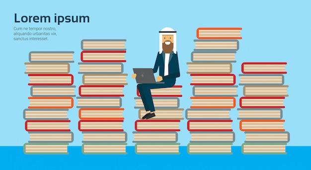 Arabski biznesmen siedzieć z laptopem na stosie książek na studium muzułmańskiego człowieka