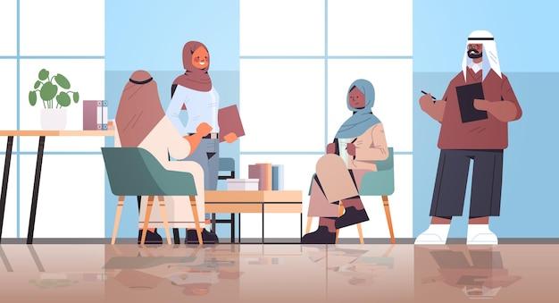 Arabski biznesmeni pracujący i rozmawiający w centrum coworkingowym spotkanie biznesowe koncepcja pracy zespołowej