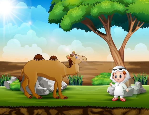 Arabski chłopiec i wielbłąd pod drzewem