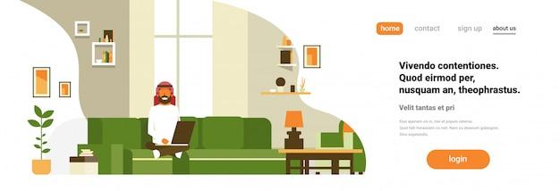 Arabski człowiek za pomocą laptopa salon wnętrze domu nowoczesne mieszkanie