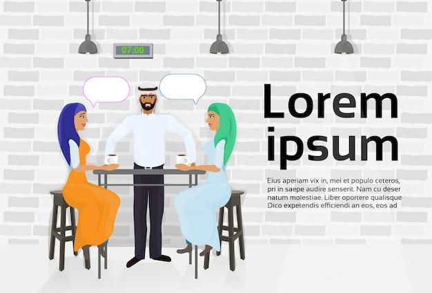 Arabski kelner obsługujących dwie kobiety muzułmańskie picia kawy w nowoczesnej kawiarni i rozmowy. szablon tekstu
