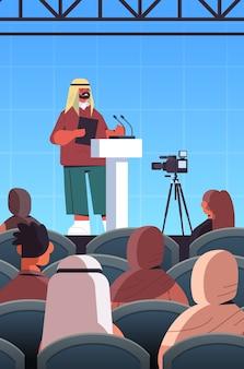 Arabski lekarz męski wygłasza przemówienie na trybunie z mikrofonem konferencja medyczna spotkanie medycyna koncepcja opieki zdrowotnej wykład wnętrze sali pionowa ilustracja