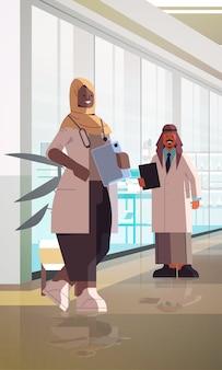 Arabski lekarze para w mundurze stojąc razem mężczyzna kobieta lekarze omawiając podczas spotkania medycyna pojęcie opieki zdrowotnej klinika wnętrze pionowe pełnej długości ilustracji wektorowych