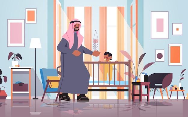 Arabski ojciec bawiący się z małym synem w łóżeczku koncepcja rodzicielstwa ojcostwa tata spędzający czas z dzieckiem w domu sypialnia wnętrze pełnej długości pozioma wektorowa ilustracja