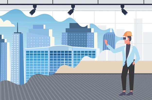 Architekt człowiek w kasku na sobie okulary cyfrowe wirtualnej rzeczywistości 3d budynku miasto model vr modelowanie zestaw słuchawkowy wizja koncepcja nowoczesne biuro wnętrze poziome pełnej długości
