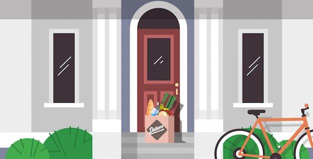 Artykuły spożywcze w paczce papierowej zamówienia pozostawione przy drzwiach produkty spożywcze ekspresowa dostawa ze sklepu lub restauracji koncepcja nowoczesnego budynku mieszkalnego na zewnątrz mieszkania poziomo
