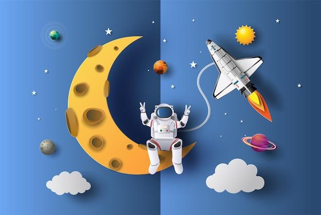 Astronauta siedzi na wyciętym z papieru kształcie półksiężyca.