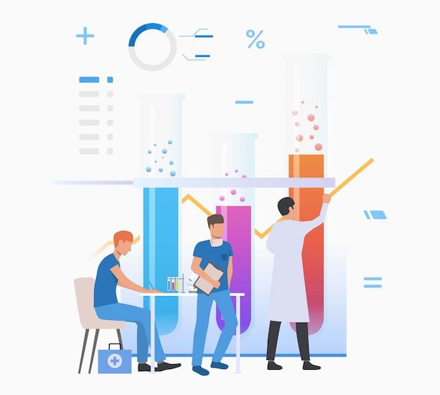 Asystenci laboratoryjni rysują wykres i pracują z probówkami