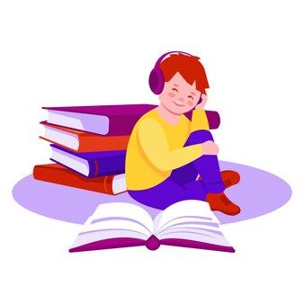 Audiobooki dla dzieci. mały chłopiec ze słuchawkami słucha audiobooka.