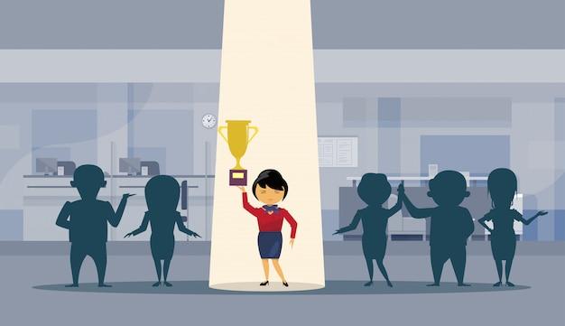 Azjatycka biznesowej kobiety chwyta złotej filiżanki pomyślny bizneswoman