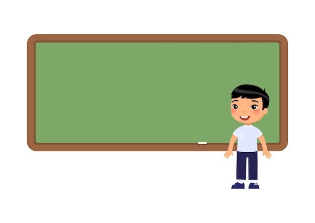 Azjatycki chłopiec w szkole stojącej w pobliżu tablicy. uczeń w pobliżu postaci z kreskówki pustej tablicy.