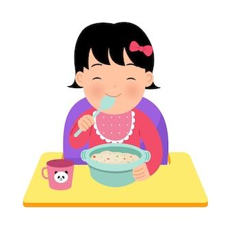 Azjatycki maluch dziewczyna siedzi na krzesełku dla dziecka i sama je miskę owsianki. szczęśliwa ilustracja rodzicielstwa. światowy dzień dziecka. na białym tle.