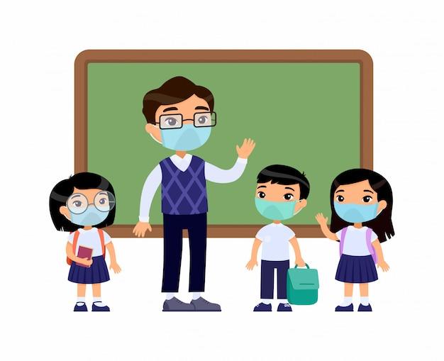 Azjatycki nauczyciel i uczniowie z maskami ochronnymi na twarzach. chłopcy i dziewczęta ubrani w mundurek szkolny i nauczyciel, wskazując na tablicy postaci z kreskówek. ochrona dróg oddechowych
