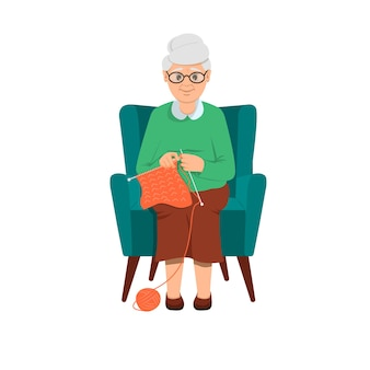 Babcia siedzi na miękkim niebieskim krześle i robi na drutach