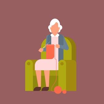 Babcia siedzi w fotelu kniting