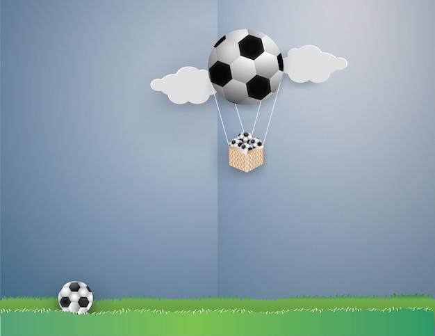 Balonowa kształtna piłka nożna z futbolami w bambusowym koszu na niebieskim niebie.