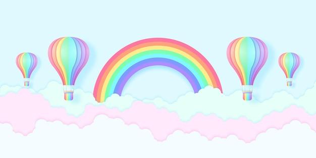 Balony na ogrzane powietrze w kolorze tęczy lecące po błękitnym niebie i kolorowe chmury z tęczą